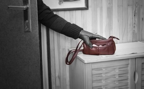 Burglar stealing a handbag