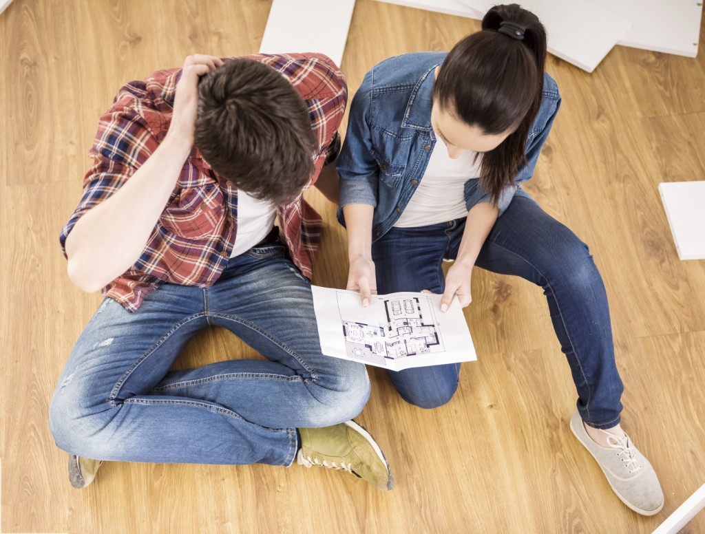 Young couple dressed casual installing furniture in new house.
