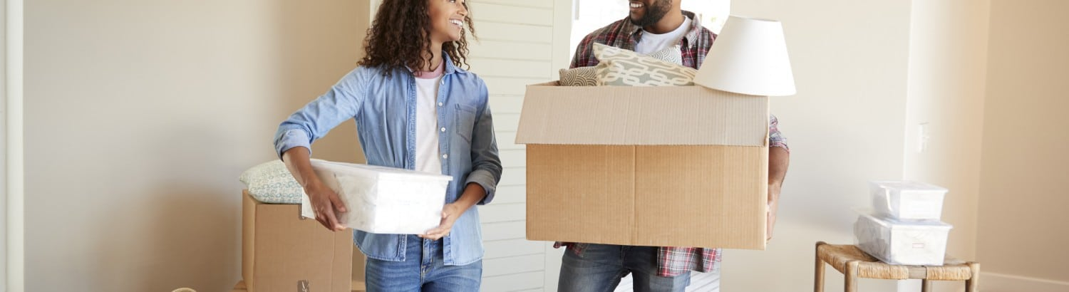 Couple Carrying Boxes Into New Home On Moving Day