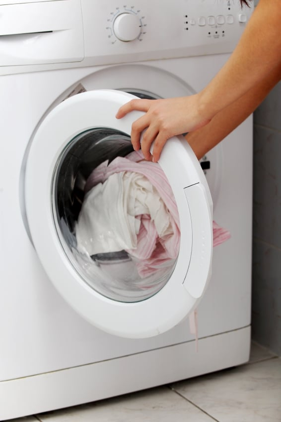 Closeup of a laundry being put into the washing machine.